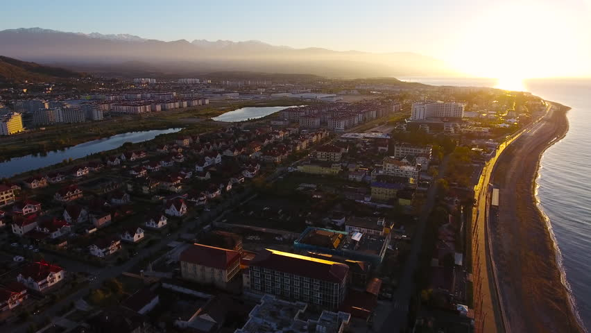 Aerial View. Flying over the city buildings houses  sea near the beach on a sunny day. Sochi Adler olympiad. Aerial drone shot. 4K 30fps ProRes (HQ) | Shutterstock HD Video #23192374