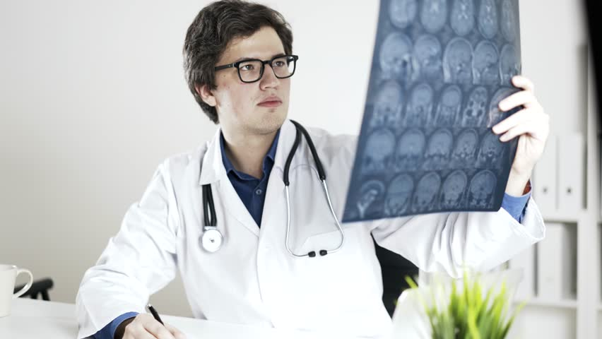 A neurologist is examining brain x-ray and making some notes. A concept of successful medical practice. Locked down real time medium shot. | Shutterstock HD Video #23211931