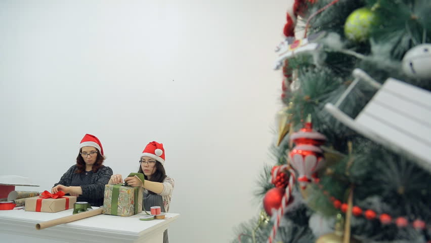 Two women prepare new year presents for Christmas holidays in office. Asian brunette woman sits wraps present box in beige paper, ties bow with green ribbon. Attentive master with brown hair, in grey | Shutterstock HD Video #23213191