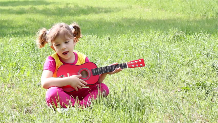 little girl sitting on grass and playing guitar - HD stock footage clip