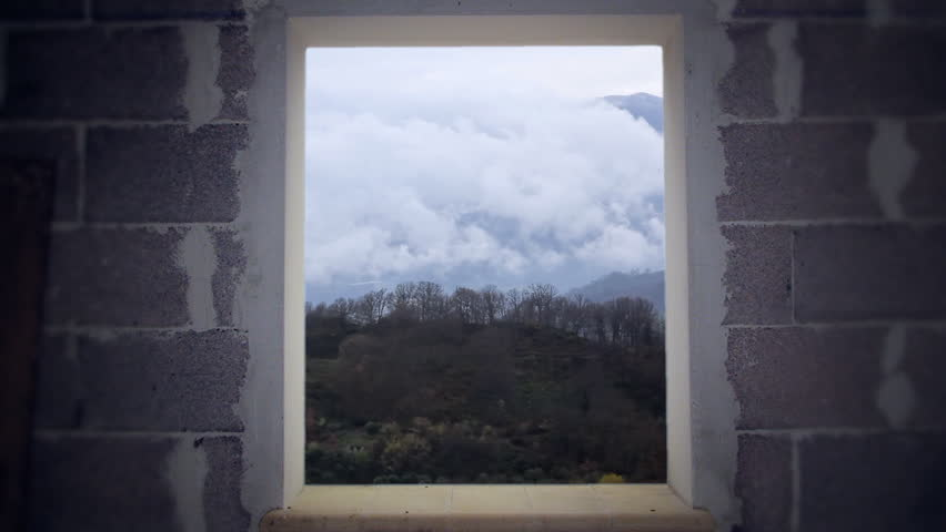 Timelapse: a mountain view in the morning. Snow-capped peaks and green bushes. Seen from a window in a bare room.