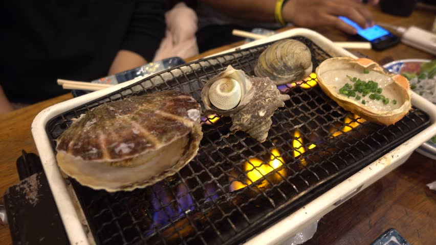 Japanese seafood barbecue , sea shell and clam shell BBQ grilled on fire  from butane gas stove ,very sweet and delicious | Shutterstock HD Video #23270638