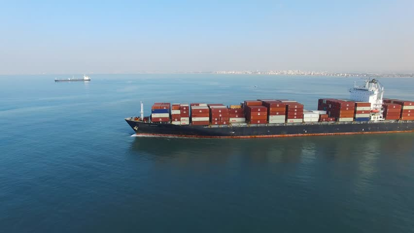 Circa, Circa, January 18, 2017: Aerial footage a large container ship leaving a commercial port, heading for it's next destination port.   Shutterstock HD Video #23280997