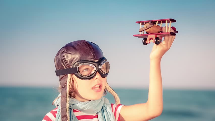 Happy child playing with toy airplane. Kid against summer sea and sky background. Travel and vacation concept | Shutterstock HD Video #23326321