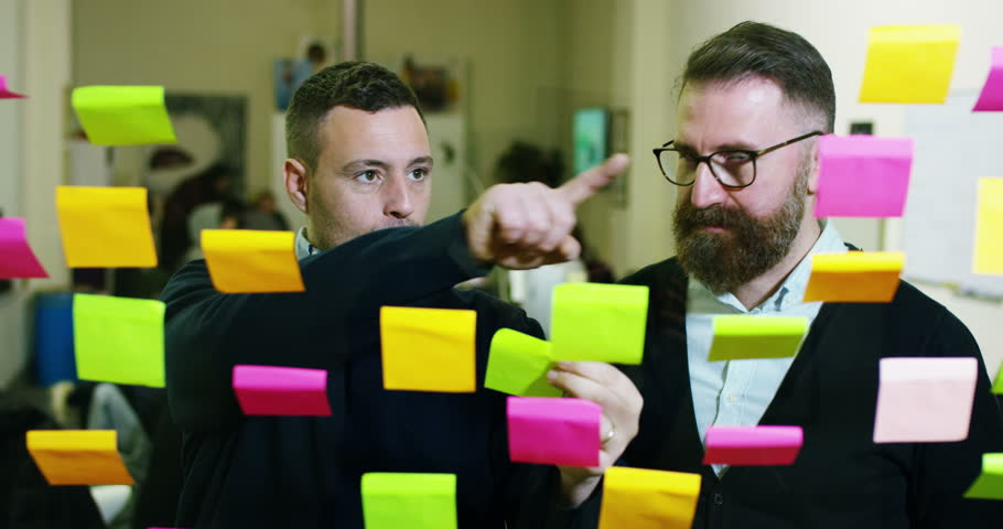 Two creative and thoughtful in a creative agency with colored and planning notes hanging from the glass and behind the working people. Concept: team work, agency, creative, business | Shutterstock HD Video #23374435