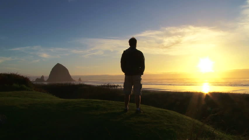 Man at Pacific Ocean near Cannon Beach looks out to sea as sun sets on beautiful day. - HD stock footage clip