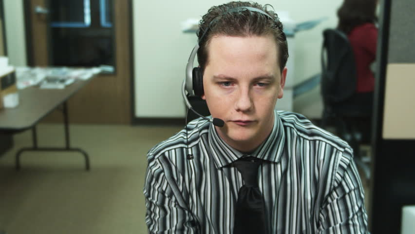 male office worker wearing headset stares at a fixed point in space; co-worker brings a folder with papers and he looks at them - HD stock video clip