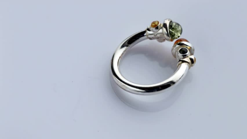 Silver ring with green and yellow amber on a light background | Shutterstock HD Video #23499724