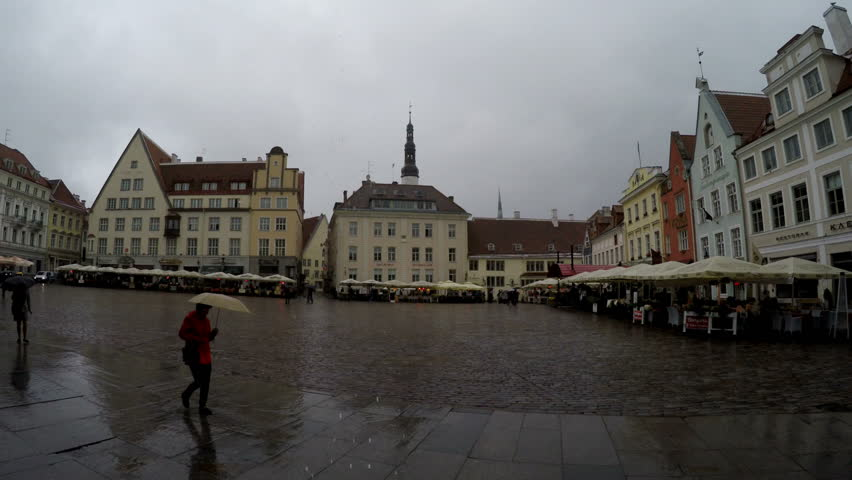 TALLINN, ESTONIA- SEPTEMBER 5, 2015 A crowd of tourists visit Town Hall Square in the rain in the Old city on September 5, 2015 in Tallinn, Estonia | Shutterstock HD Video #23525131