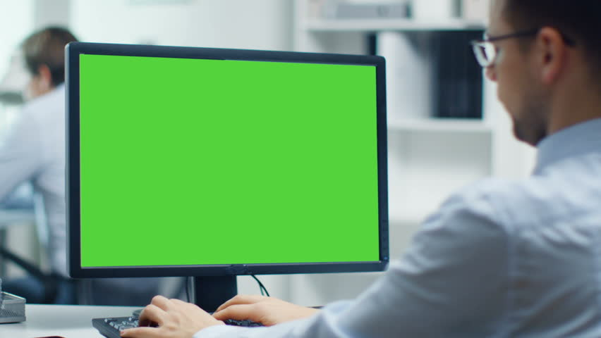 Businessman Working on a Personal Computer with Green Screen on. Colleague in the Background. Office is Bright and Modern. Shot on RED Cinema Camera 4K (UHD). | Shutterstock HD Video #23570905