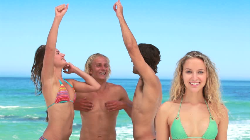 Four friends partying as a blonde girl looks at the camera and smiles - HD stock video clip