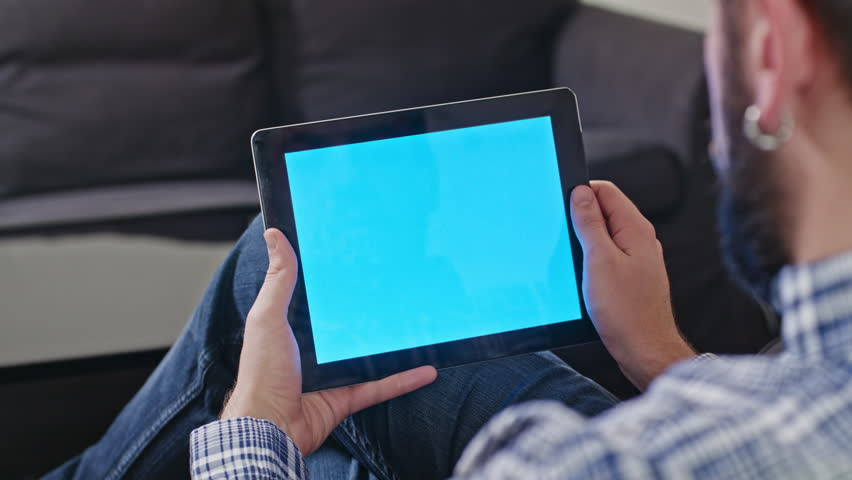 Close-up rear view of Man uses a digital tablet with a blue screen at home. In the background is neither black coffee table and sofa | Shutterstock HD Video #23716030