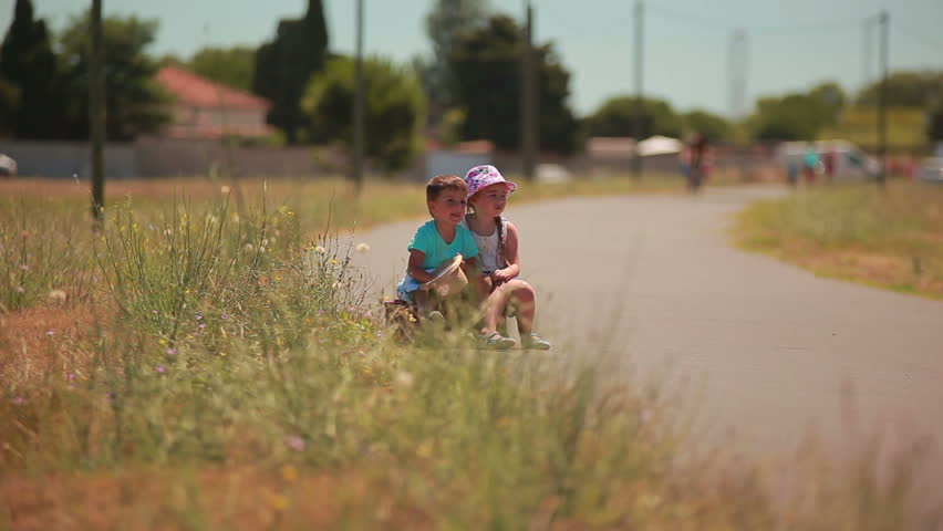 Tired boy and girl hitchhiking at the road with a suitcase | Shutterstock HD Video #23767078