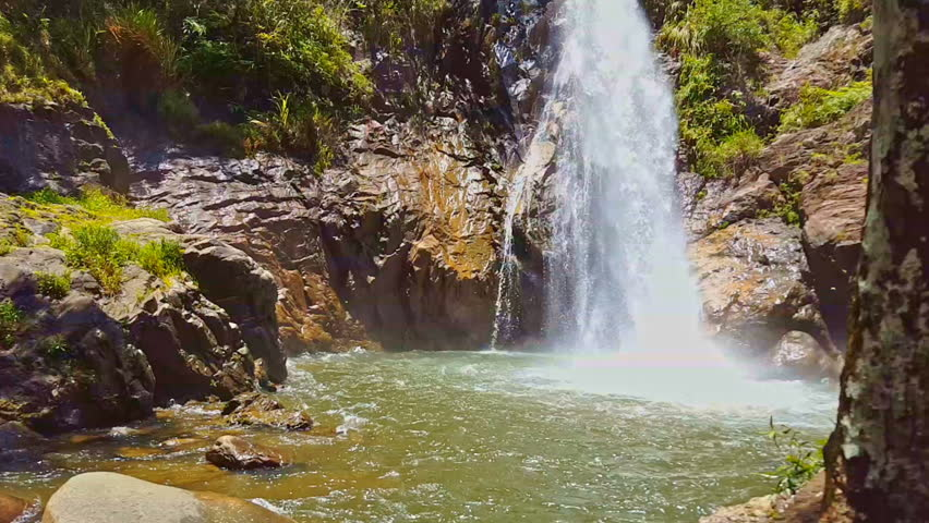 High powerful waterfall falls in deep pond among big rocks in tropical jungle | Shutterstock HD Video #23794618
