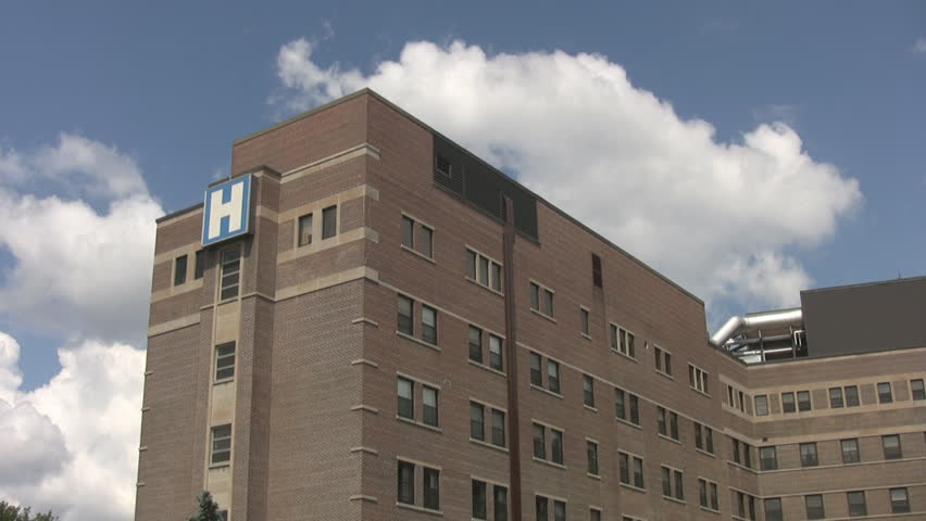 A hospital with blue sky and timelapse clouds in the background.