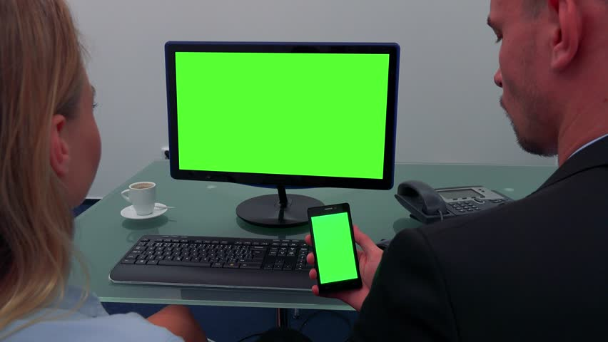 A man and a woman sit at a desk in an office and look in turns at a computer screen and a smartphone (both green screen) | Shutterstock HD Video #23863234