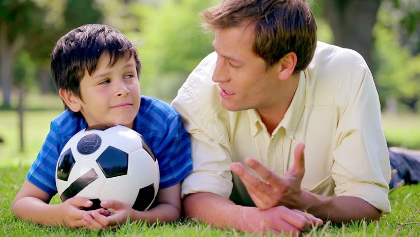 Happy father and son lying on the grass with a soccer ball in the countryside - HD stock video clip