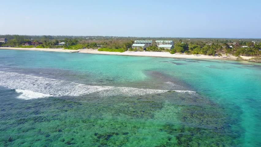 Aerial view of Spotts beach, public beach, Grand Cayman. aerial clip moving from off shore over the barrier reef toward the beach and a pier. Crystal clear caribbean water, coral and beach.