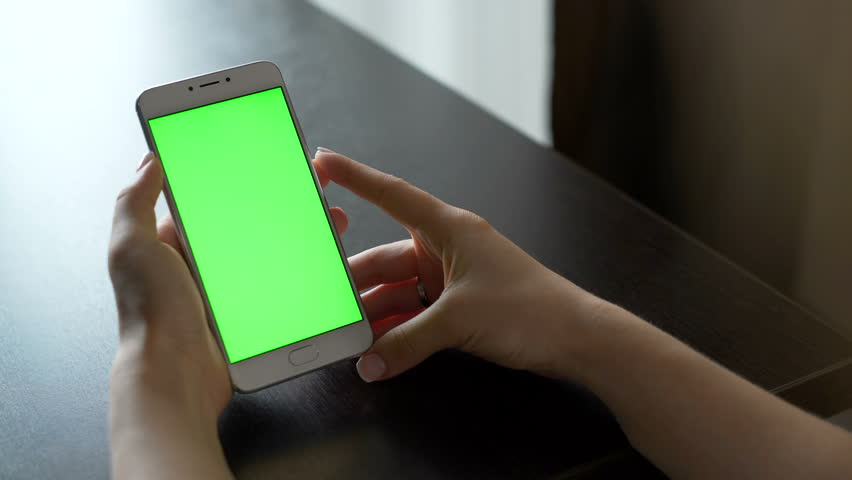 One person use cellular telephone with touch green screen for browsing social networks and communicating closeup. Girl, holding in hand portable gadget close up, as image of tech accessibility concept | Shutterstock HD Video #23974870