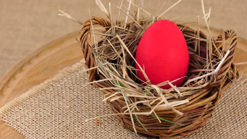 Close up shot of a red Easter egg in woven basket with dry grass rotating against beige background. Egg in a nest concept. | Shutterstock HD Video #24027772