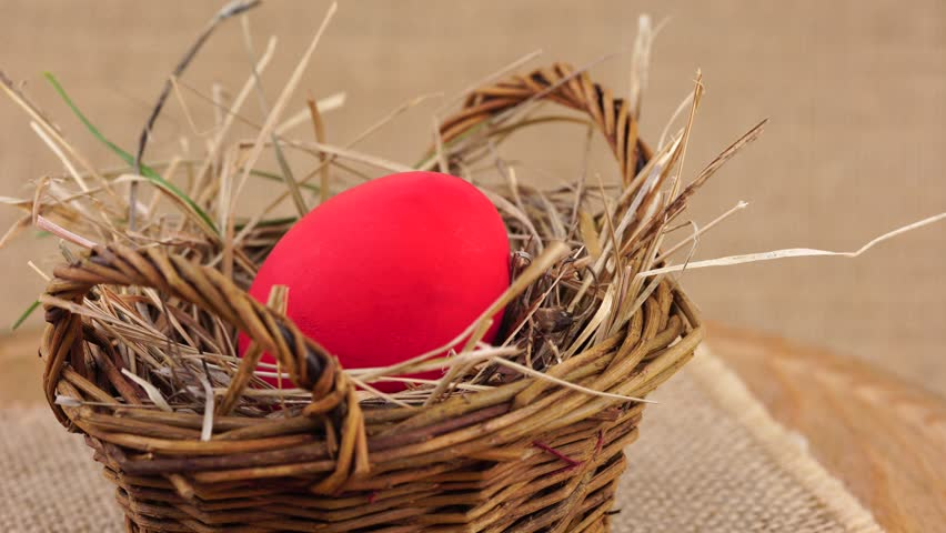 Close up shot of a red Easter egg in woven basket with dry grass rotating against beige background. Egg in a nest concept. | Shutterstock HD Video #24027781