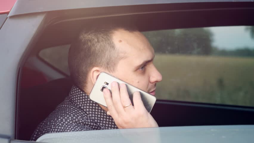 Handsome businessman sitting in car talking on cell phone. 3840x2160 | Shutterstock HD Video #24029797