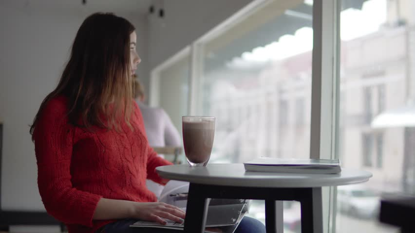 Beautiful woman reading newspaper, drinking coffee in cafe | Shutterstock HD Video #24038995
