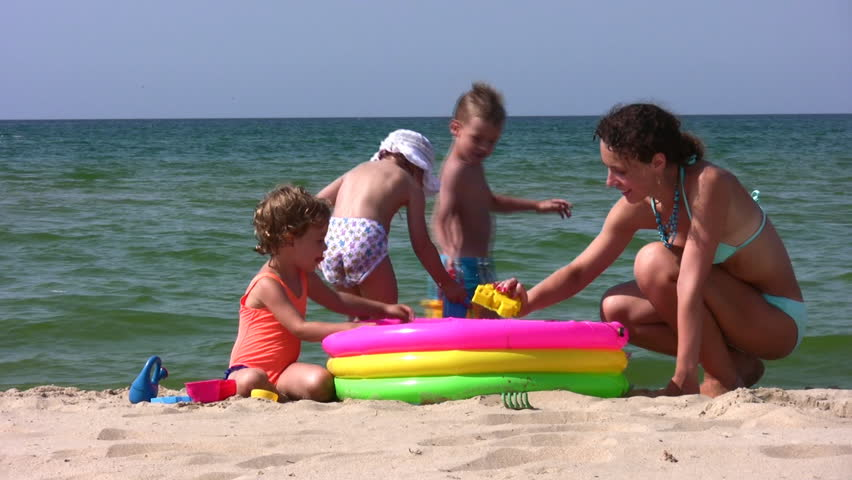 mother with children play on beach  - HD stock video clip