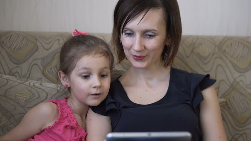 Young caucasian mom fun playing on the tablet with his little daughter in a computer game. Cheerful stay in spare time. | Shutterstock HD Video #24105109