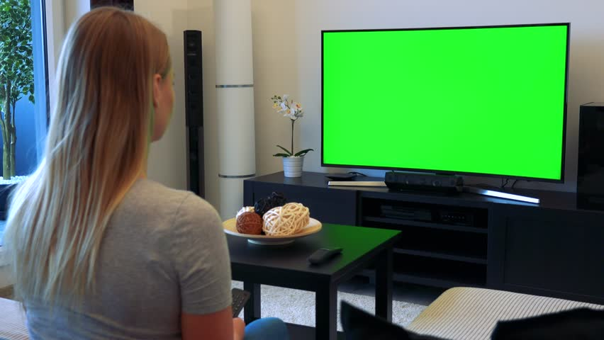 A blonde woman sits on a couch in a living room, watches a TV with a green screen and uses a TV controller | Shutterstock HD Video #24114181