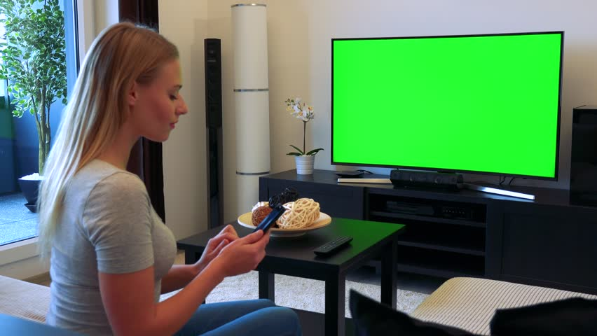 A young, beautiful woman sits on a couch in front of a TV with a green screen in a living room and works on a smartphone | Shutterstock HD Video #24114190