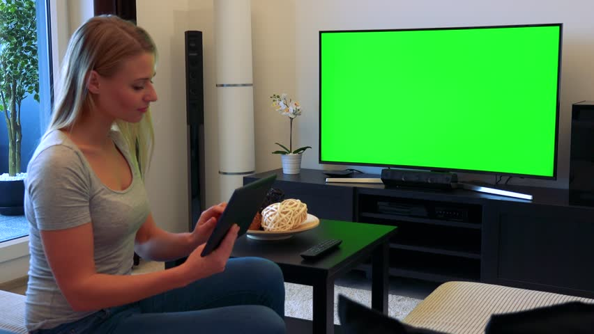 A young, beautiful woman sits on a couch in front of a TV with a green screen in a living room and works on a tablet | Shutterstock HD Video #24114208