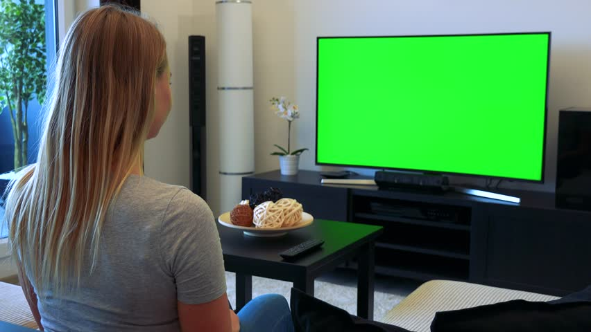 A young, beautiful woman sits on a couch in a living room and watches a TV with a green screen, then turns and shows a thumb up at the camera with a smile | Shutterstock HD Video #24114244