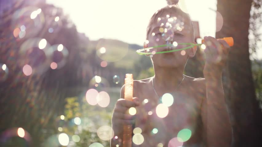 Young handsome joyful boy blowing bubbles outdoors on sunny day in summer on sunshine background with blurred beautiful bokeh. 1920x1080 | Shutterstock HD Video #24114406