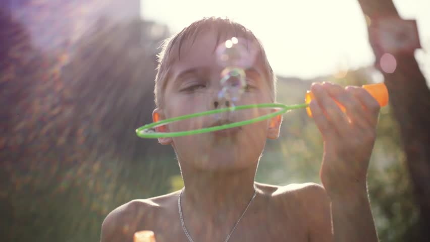 Young boy blowing bubbles outdoors on sunny day in summer on sunshine background with blurred beautiful bokeh. 1920x1080 | Shutterstock HD Video #24114415