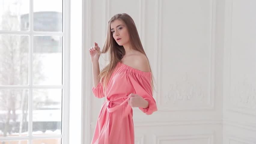 Playful fashion model in pink summer dress posing near window in studio   Shutterstock HD Video #24122686