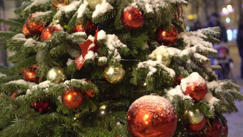 New year city decoration. Read balls on snow Christmas tree. Winter evening night illumination. Pedestrian street. People walk at blur background. Moscow Russia. Slow tilt. | Shutterstock HD Video #24127258