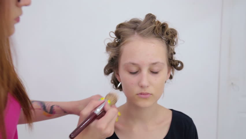 Makeup artist applying liquid tonal foundation on the face of teen girl in white make up room. Beauty and fashion concept   Shutterstock HD Video #24132100