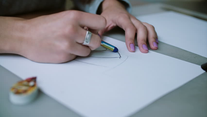 Woman sitting at table, holding pencil and coloring sketch of shoes on paper. Slider right, camera goes by circle. 4K | Shutterstock HD Video #24141649