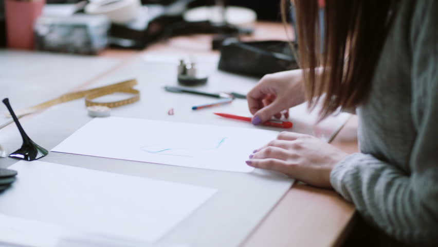 Young designer sitting at the table and drawing the sketch of blue shoes. Woman erase on paper. Side view. 4K | Shutterstock HD Video #24141658