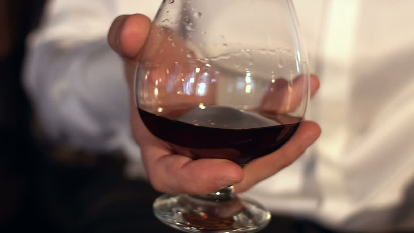 Man stir slowly cognac in the glass, slow motion.Glass of whiskey in male hands. | Shutterstock HD Video #24149281