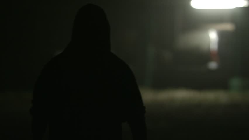 Back view of young man walking determined to train in front of old garage at night. | Shutterstock HD Video #24198151