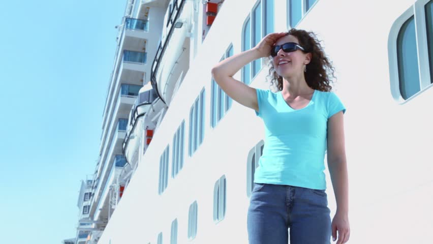 Woman in sunglasses stands and smiles near board of huge liner - HD stock footage clip