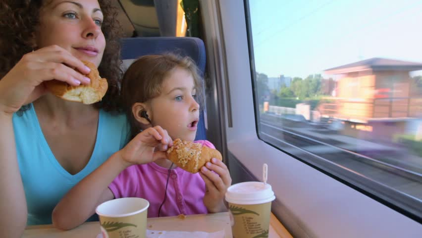 Mother with her little daughter eat marzipans and watch to train window