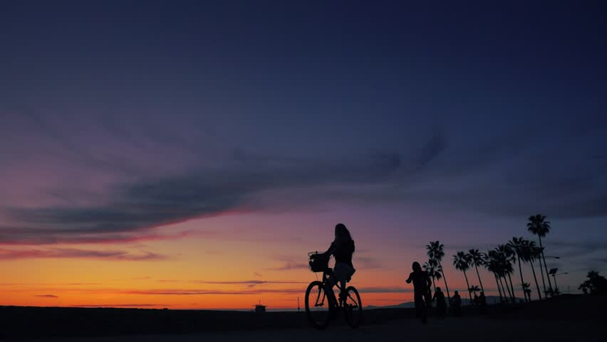 Bicyclists cruising in front of sunset as silhouettes between Santa Monica and Venice Beach in Los Angeles, California. Slow motion. | Shutterstock HD Video #24223999