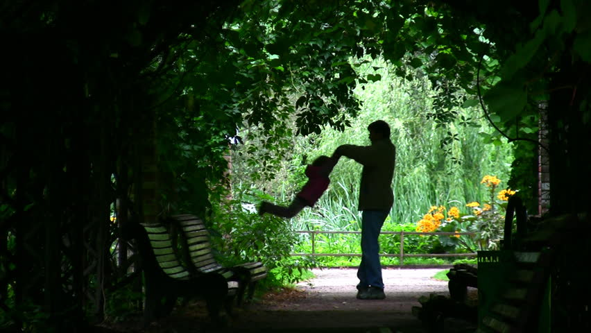 Father Rotatting his Daughter : Silhouette in green arch  - HD stock footage clip