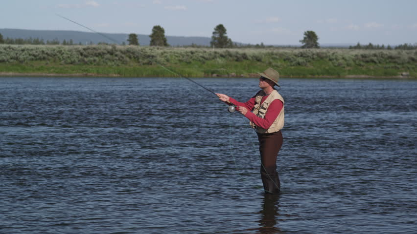 Man fly fishing in the henrys fork of the snake river for Henry s fork fishing