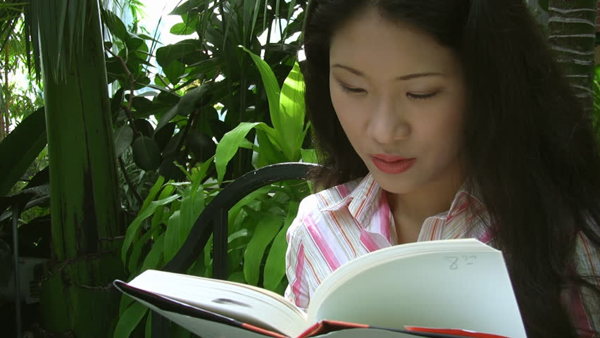 An attractive young asian woman reads a book, in a greenhouse. - HD stock footage clip