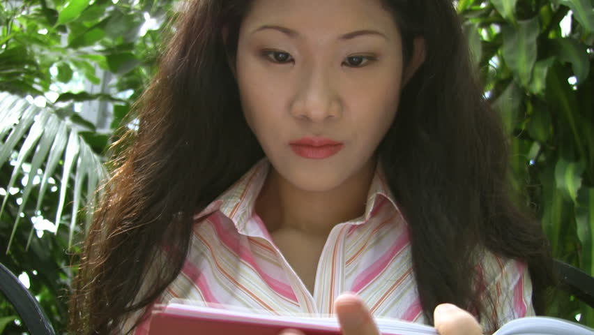 An attractive young asian woman writes, in a greenhouse. - HD stock video clip