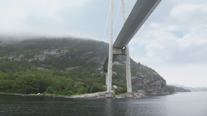 Huge pendant bridge at coast with forest on mountains under cloudy sky
